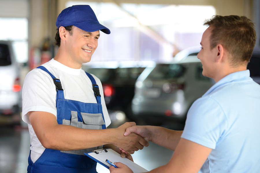 Mechanic and car owner shaking hands
