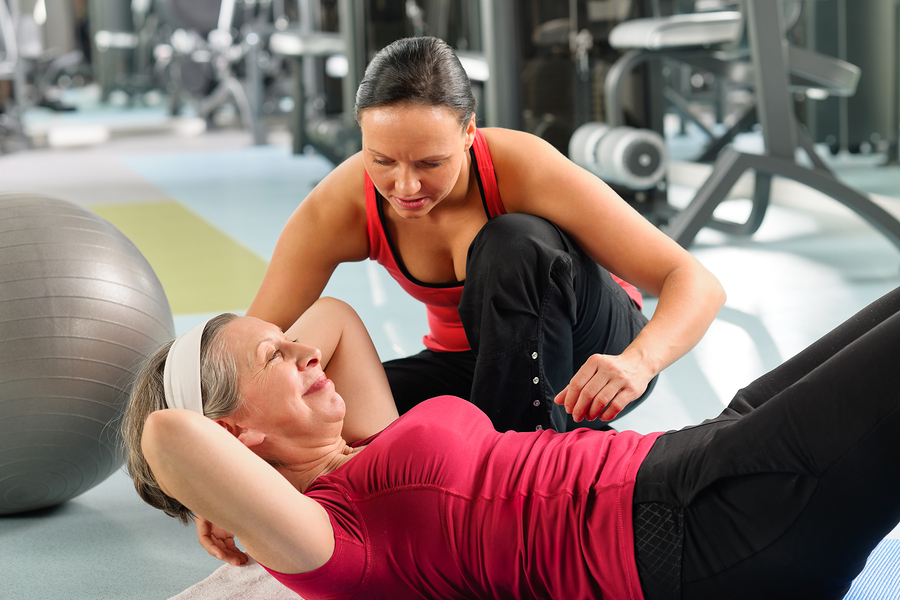 Senior woman exercising with personal trainer