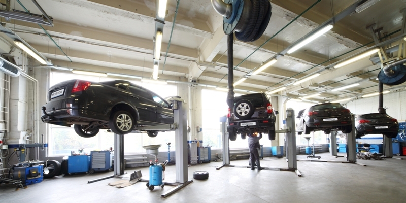A vehicle service station's garage facility with vehicles on car lifts