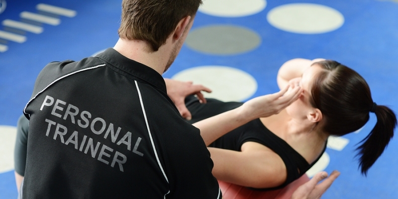 A personal Trainer assisting a woman client