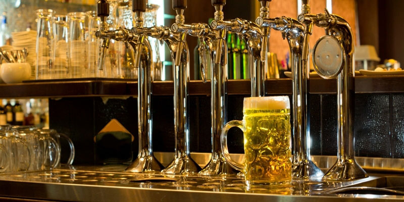 A row of beer taps and a mug of beer in a bar, pub, or tavern