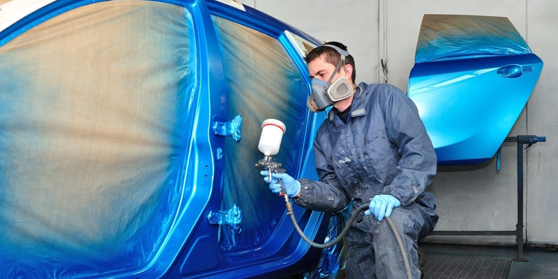 A mechanic applying blue paint on a car's body