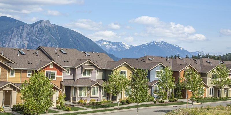 A row of duplex houses with a mountain range in the background