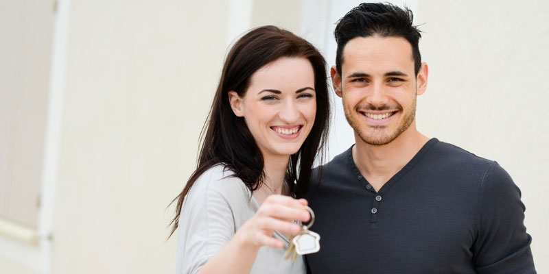A couple happily showing the keys to their new home