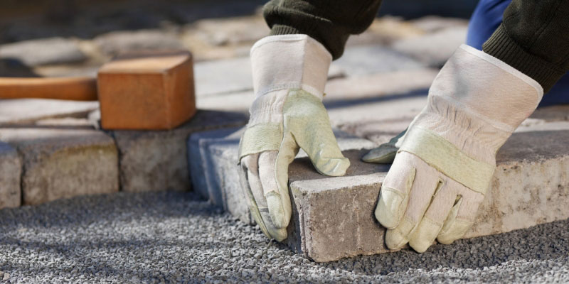 Close-up image of gloved hands handling stone blocks