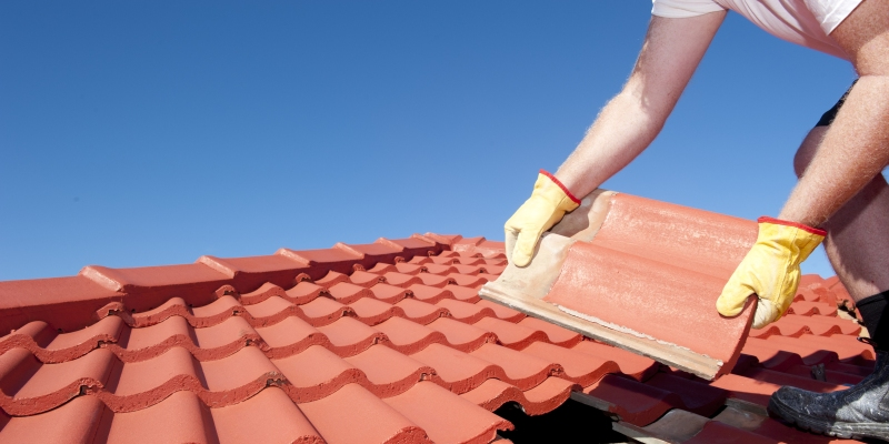A roofer working on roof tiles